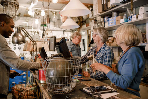 Male customer standing with female owners at checkout in hardware store - MASF14059
