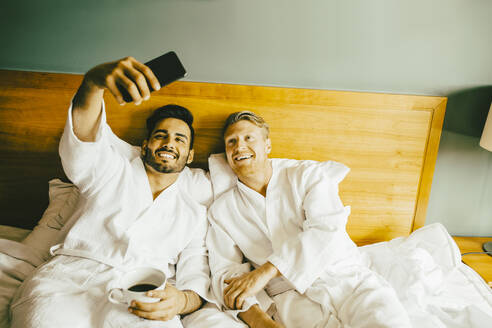 Smiling gay man holding coffee cup while taking selfie with boyfriend at hotel room - MASF14155