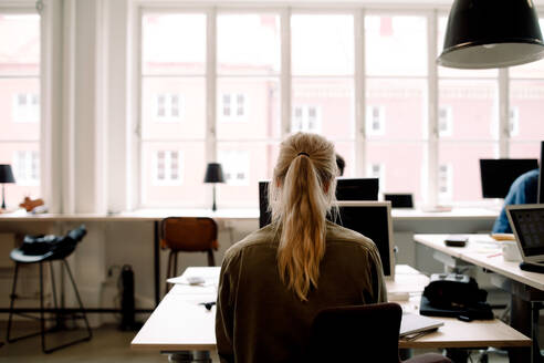 Rear view of businesswoman working in creative office - MASF14234