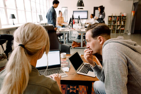 Male and female professionals working over laptop while sitting at office desk - MASF14291