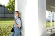 Portrait of smiling young woman  leaning against wall - FLLF00339
