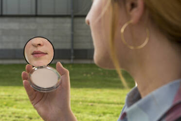 Young woman with nose piercing looking at beauty mirror in her hand - FLLF00342