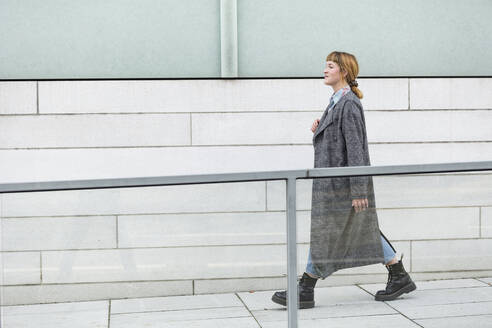 Self-confident young woman wearing grey coat walking on a ramp - FLLF00348