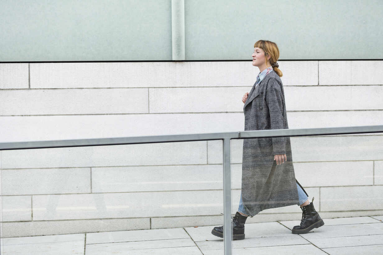 Self-confident young woman wearing grey coat walking on a ramp - FLLF00348 - FL/Westend61