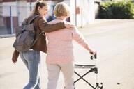 Granddaughter assisting her grandmother walking with wheeled walker - UUF19504