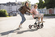 Granddaughter and her grandmother having fun with wheeled walker - UUF19510