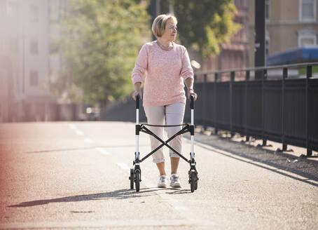 Senior woman with wheeled walker on footbridge - UUF19519