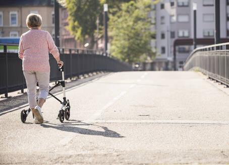 Senior woman with wheeled walker on footbridge - UUF19522