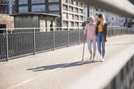 Granddaughter and her grandmother walking on footbridge - UUF19528