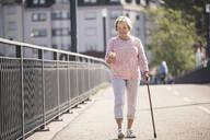 Senior woman walking on footbridge, using walking stick - UUF19537