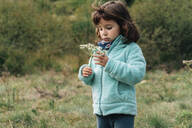 Portrait of little girl with wildflower in autumn - GEMF03276