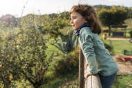Portrait of smiling little girl leaning on wooden fence - GEMF03279