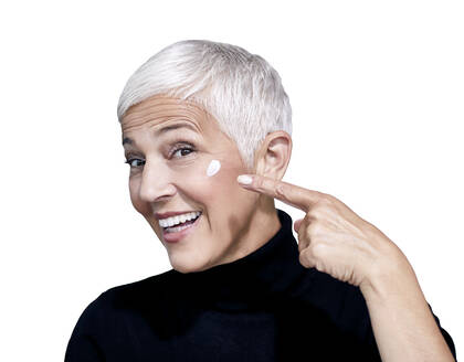 Portrait of mature woman with beauty cream on her face against white background - RAMF00094