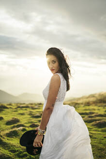 Young woman wearing white dress on viewpoint at sunset - MTBF00163