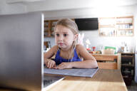Portrait of little girl in the kitchen at home staring at laptop - KMKF01132