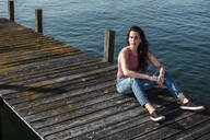 Young woman sitting on jetty looking at distance, Lake Starnberg, Germany - WFF00152