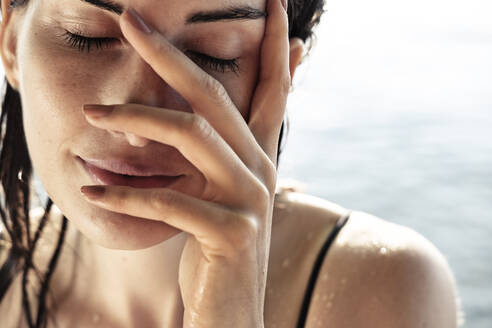 Woman with eyes closed and hand on her face after bathing, close-up - WFF00161