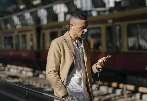Man standing at train station using smartphone and earphones, Berlin, Germany - AHSF01101
