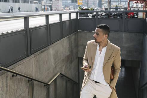 Businessman leaving underground station using earphones and smartphone - AHSF01107