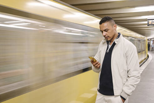 Portrait of man standing in front of driving underground train looking at cell phone, Berlin, Germany - AHSF01125