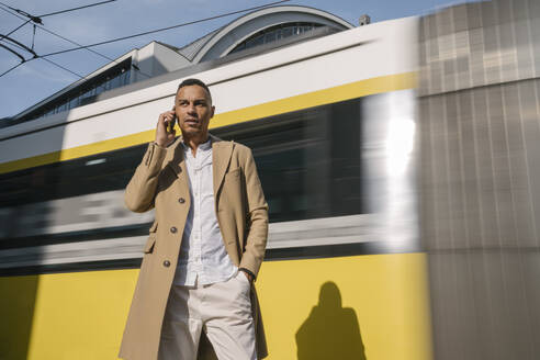 Portrait of businessman on the phone standing in front of driving tramway, Berlin, Germany - AHSF01134
