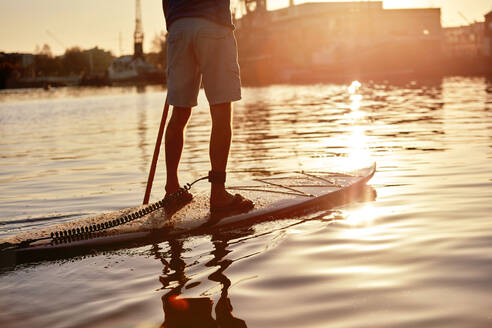 Man standing on paddleboard on river at dawn, shot from behind - MINF12793