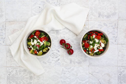 Bowls of salad with beluga lentils, tomatoes, paprika, zucchini, feta cheese, mint and parsley - LVF08422