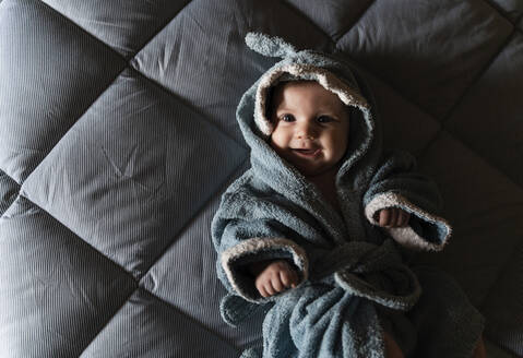 Portrait of happy baby girl lying on bed wrapped with shark shaped towel after bath - GEMF03290