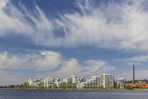 Finland, Lahti, Clouds over Vesijarvi lake and modern residential buildings in spring - MELF00209