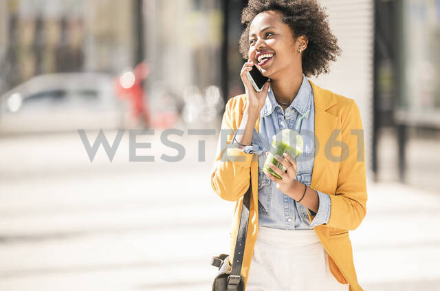 Happy young woman on the phone in the city - UUF19582 - Uwe Umstätter/Westend61
