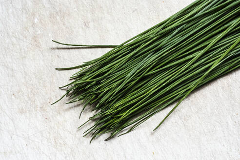 High angle close up of a bunch of fresh chives on white background. - MINF13147