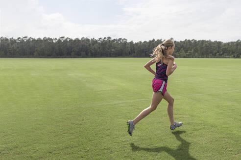 Teen girl cross country runner practicing sprints at soccer field - CAVF68680