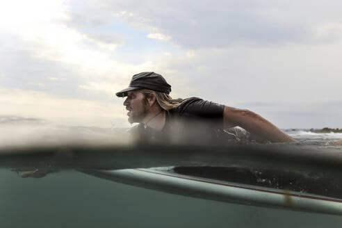 Man lying on surfboard on the sea - CAVF68722