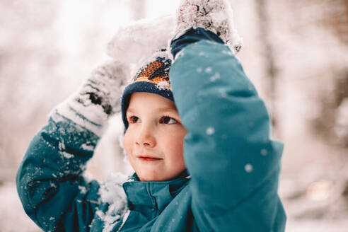 Happy boy playing with snow during winter - CAVF68782
