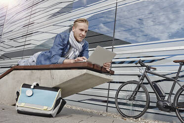 Student lying on bench and using laptop - RORF01963