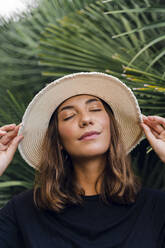 Portrait of young woman with eyes closed wearing summer hat - AFVF04173