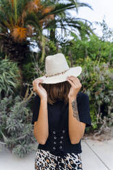 Fashionable young woman wearing summer hat covering face with her hair - AFVF04179