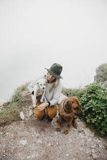 Young woman with two dogs on viewpoint - LHPF01134