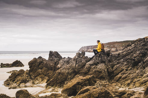 Young woman wearing yellow rain jacket sitting on rock at the beach, Bretagne, France - UUF19647