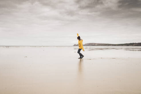 Young woman wearing yellow rain jacket at the beach, Bretagne, France - UUF19653