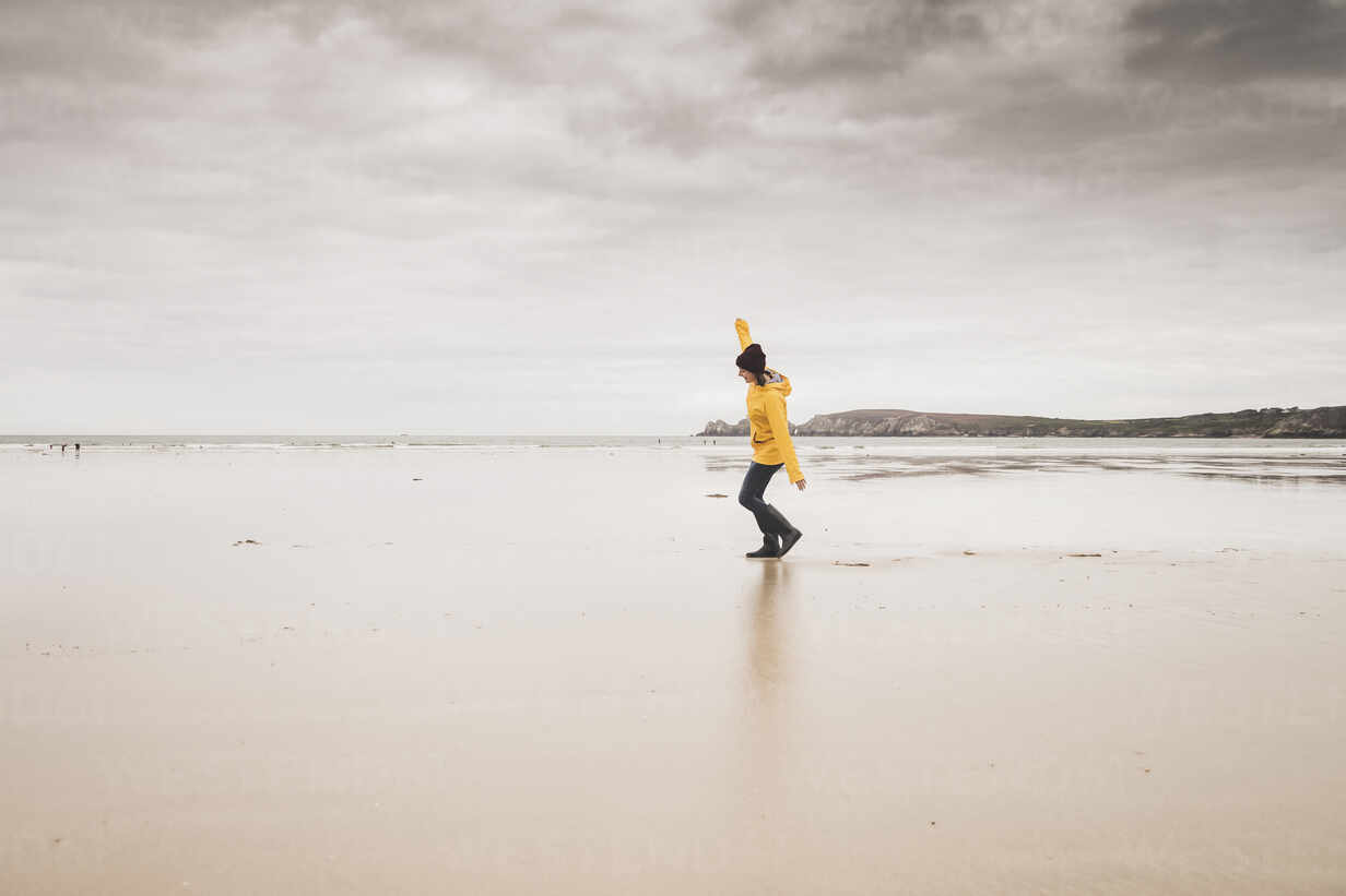 Young woman wearing yellow rain jacket at the beach, Bretagne, France - UUF19653 - Uwe Umstätter/Westend61