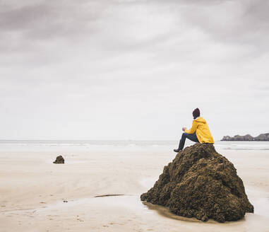 Young woman wearing yellow rain jacket sitting on rock at the beach, Bretagne, France - UUF19662