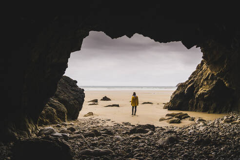 Young woman wearing yellow rain jacket at the beach at rock cave, Bretagne, France - UUF19665