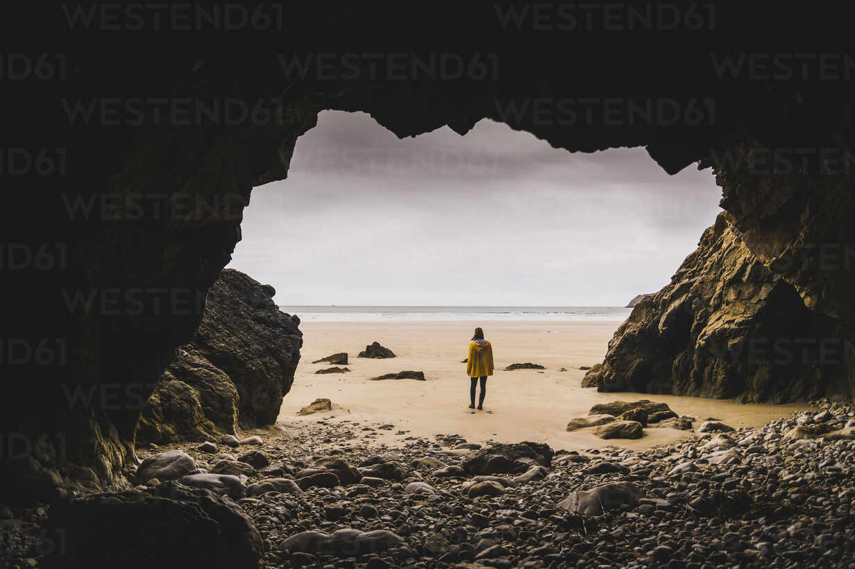 Young woman wearing yellow rain jacket at the beach at rock cave, Bretagne, France - UUF19665 - Uwe Umstätter/Westend61