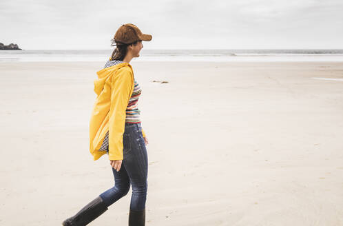 Young woman wearing yellow rain jacket at the beach, Bretagne, France - UUF19668
