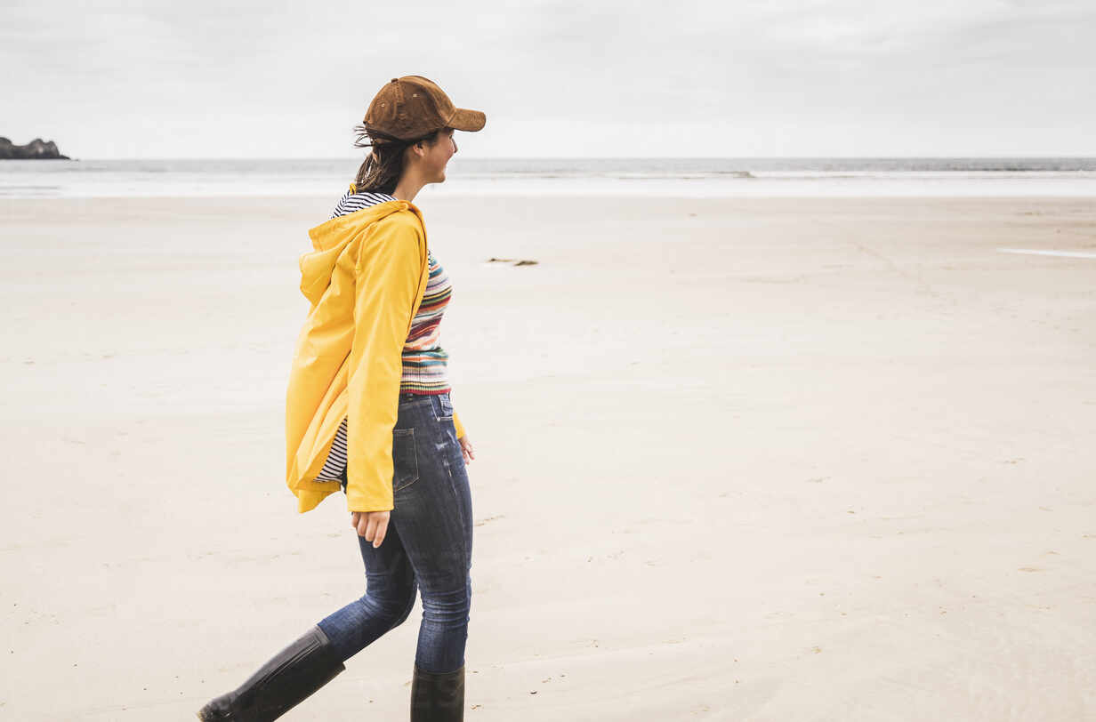 Young woman wearing yellow rain jacket at the beach, Bretagne, France - UUF19668 - Uwe Umstätter/Westend61