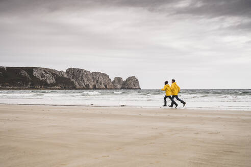 Young woman wearing yellow rain jackets and running at the beach, Bretagne, France - UUF19671
