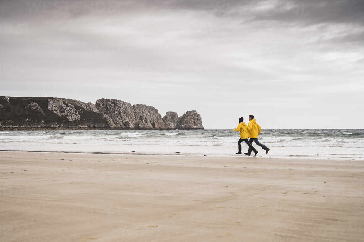 Young woman wearing yellow rain jackets and running at the beach, Bretagne, France - UUF19671 - Uwe Umstätter/Westend61