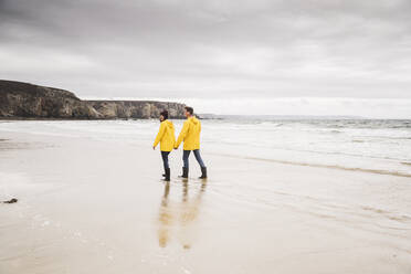 Young woman wearing yellow rain jackets and walking along the beach, Bretagne, France - UUF19674