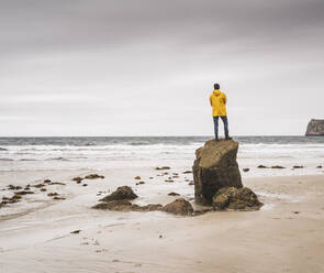 Young man wearing yellow rain jacket at the beach and standing on rock, Bretagne, France - UUF19680
